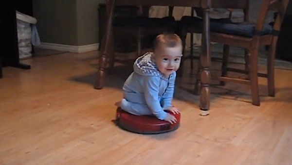 baby riding a roomba